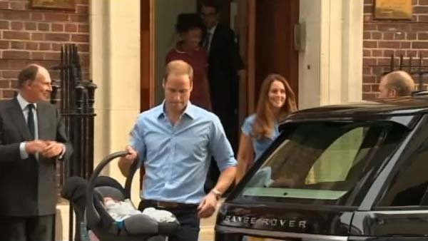 Prince William puts his newborn son into the car before he drives he and his wife Catherine home from the hospital. (Source: CNN)