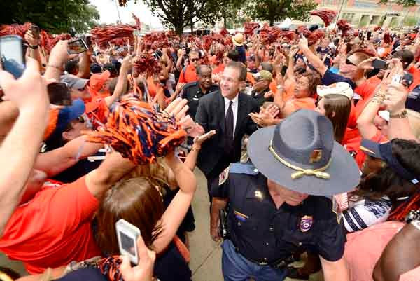 New Auburn head coach Gus Malzahn walks through a throng of Auburn fans on his way to the stadium Saturday. Malzahn was one of four SEC coaches making his debut this week and one of three to win. (Source: Todd Va