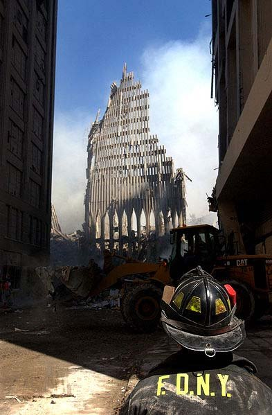 A New York City fire fighter looks up at what remains of the World Trade Center after its collapse during the Sept. 11 terrorist attack. (Source: Wikimedia Commons/U.S. Navy)