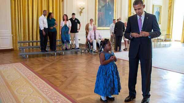 President Barack Obama writes an excuse for a little girl who was visiting the White House with her veteran father. (Source: Official White House Photo/Pete Souza)