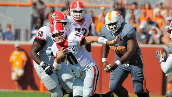 Quarterback Aaron Murray, who became the SEC's all-time passing leader on Saturday, escapes pressure from Tennessee defenders. (Source: Georgia Athletics/John Kelley)
