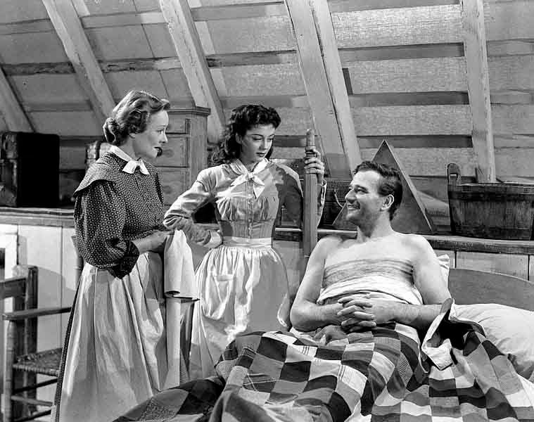 From left to right, Irene Rich, Gail Russell and John Wayne, are shown in a scene from 'Angel and the Badman.' (Source: Wikimedia Commons)