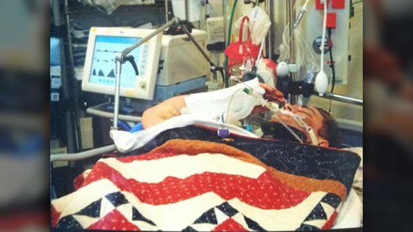 Cpl. Joshua Hargis gives 'salute seen around the world' with his heavily injured right hand from a military bed in Afghanistan. (Source: Guardian of Valor/Taylor Hargis)