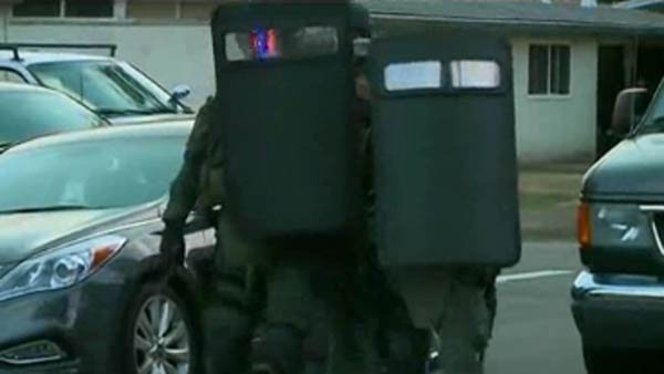 Officers carrying shields surrounded a home where a suspected gunman was holed up. (Source: KOVR)