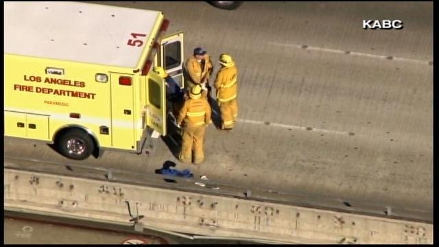 Responders place someone on a gurney into an ambulance Friday outside Los Angeles International Airport. (Source: KABC/CNN)