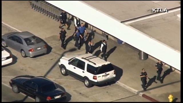 Members of law enforcement walk outside LAX. (Source: KTLA/CNN)