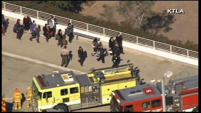 People walk outside LAX after a shooting Friday. (Source: KTLA/CNN)