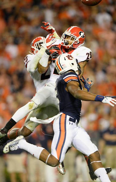 Georgia safeties Josh Harvey Clemons (25) and Tray Matthews (28) make a play on a pass intended for Auburn's Ricardo Louis (5). (Source: Todd van Emst/Auburn University)