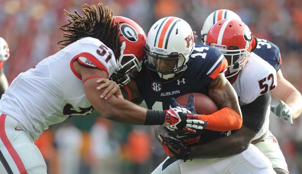 Auburn quarterback Nick Marshall (14) leads the SEC's top rushing attack and has pulled out dramatic wins in the last two weeks with crucial passing plays. (Source: Georgia Athletics)