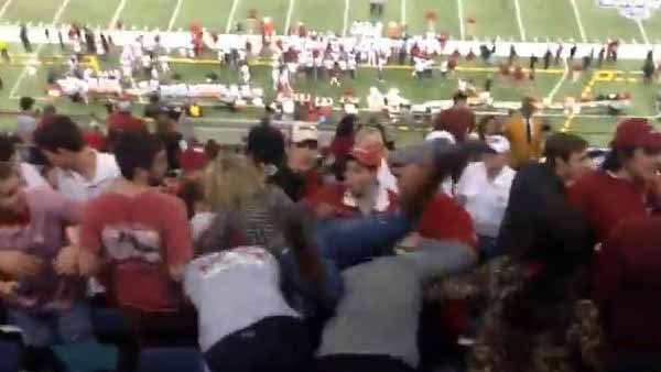 Angry Bama fan leaps a row of Oklahoma fans in a fight caught on video. (Source: YouTube/Kellikay)
