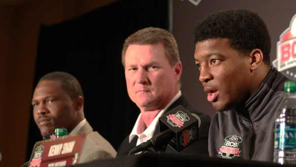 Florida State quarterback Jameis Winston answers questions for the media Friday while offensive coaches Randy Sanders, center, and Lawrence Dawsey look on. (Source: George Jones/RNN)