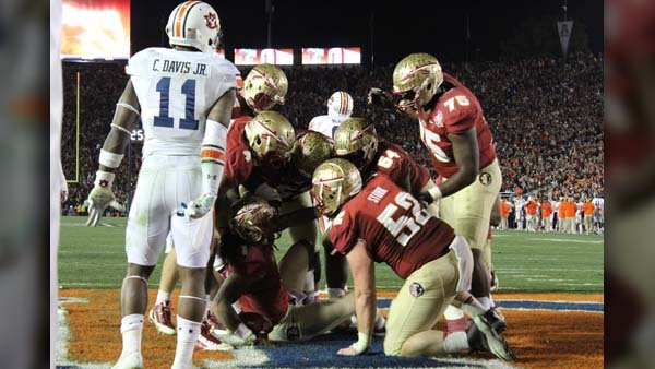 Auburn defensive back Chris Davis looks on while FSU players pick Kelvin Benjamin up after Benjamin caught the winning touchdown. (Source: George Jones/Raycom News Network)