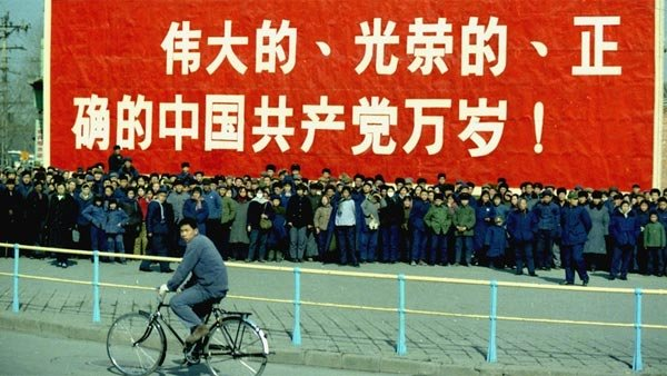 Spectators stand in front of a large sign as they await Nixon's motorcade during the president's visit to China. (Source: National Archives/Wikimedia Commons)