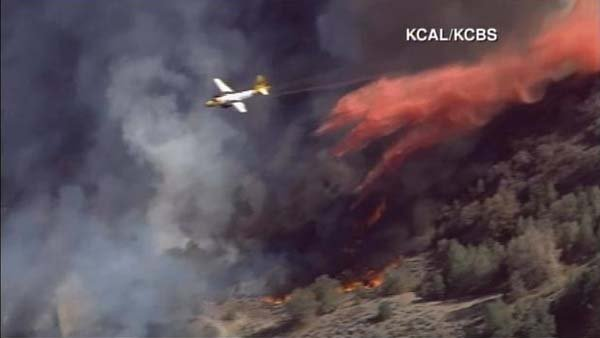 Airplanes and helicopters are dumping water in an attempt to contain a fast moving brush fire near Los Angeles. (Source: KCAL/CNN)