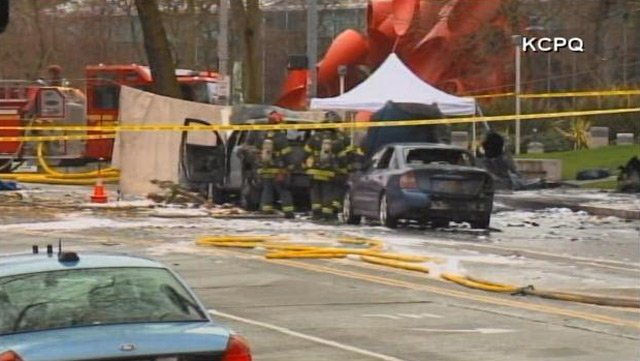 Seattle firefighters survey two cars left charred by a helicopter crash near the Space Needle on Tuesday. (Source: KCPQ)