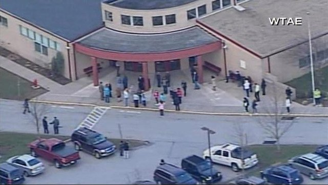 Students and faculty stand outside Franklin Regional High School in Murrysville, PA, after a student stabbed several people inside. (Source: WTAE/CNN)