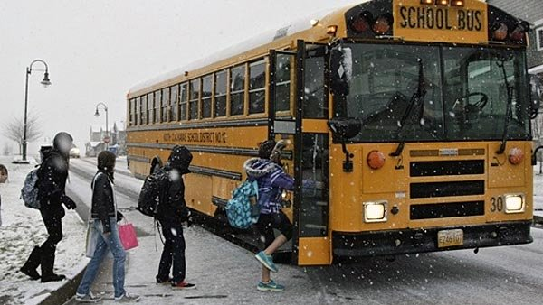 Students board a school bus during snowy weather. (Source: Thomas Boyd/The Oregonian/MGN)