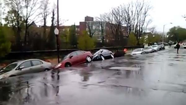 Cars tilt precariously just before a landslide caused them to fall on train tracks below. (Source: ToddTesla/YouTube)