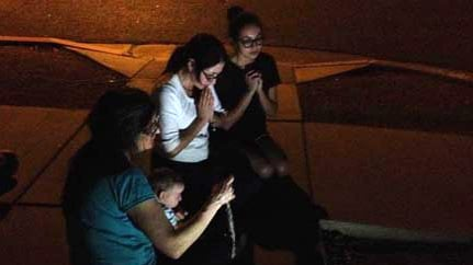 Women pray the Rosary at the Mother of Mercy Mission Catholic Church after a priest was found dead. (Source: KPHO)