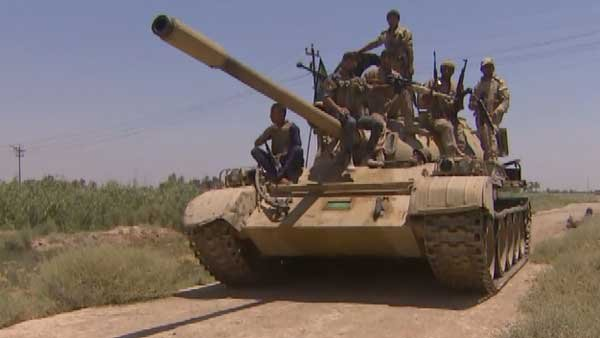 Iraqi troops ride a tank that is moved in position to get ready for any ISIS terrorist assault on Baghdad. (Source: CNN)
