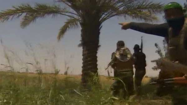 Shiite militia allied with Iraqi forces point toward ISIS positions about 15 miles from Baghdad's airport. (Source: CNN)