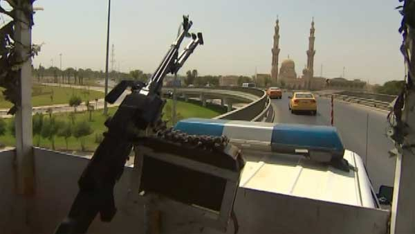 An Iraqi patrol keeps an eye out for terrorists and bombers as it moves through the capital of Baghdad.  (Source: CNN)