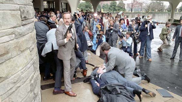 James Brady was on of four people shot on March 30, 1981. Brady is in the bottom of the photo with two men tending to him after shots rang out. (Source: Ronald Reagan Library)