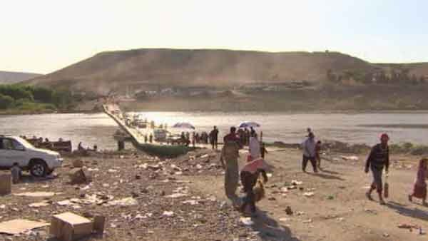 Yazidis cross river from Mount Sinjar, Iraq to Syria and back into Iraq. (Source: CNN)