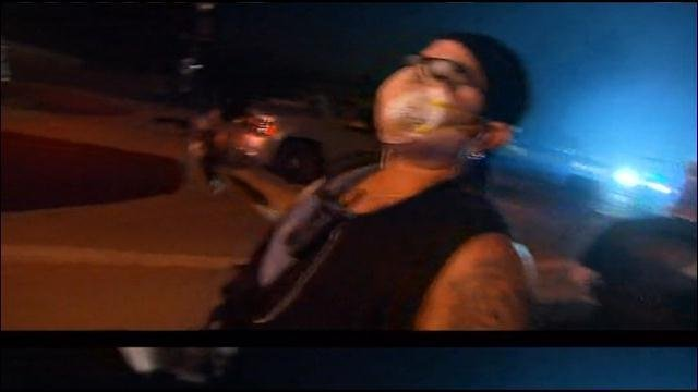 A person stands in Ferguson, MO with a mask over their face after police fire tear gas canisters and flash bombs on Monday night in Ferguson, MO. (Source: CNN)