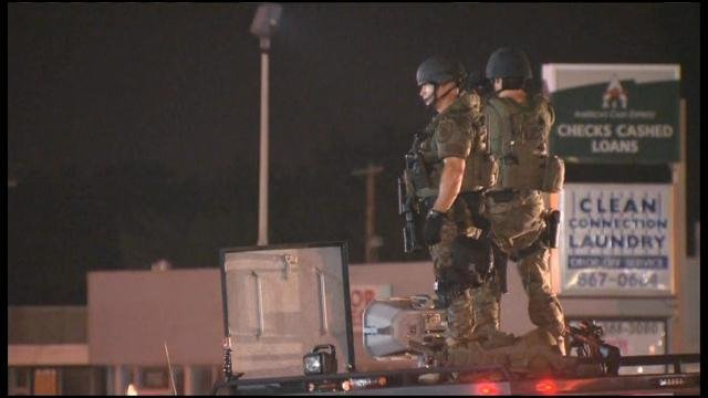 Armored personnel stand atop an armored vehicle late Monday night in Ferguson, MO. (Source: CNN)