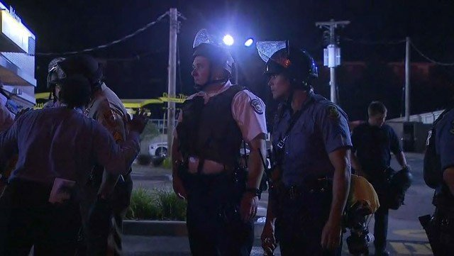 Police in riot gear stand in the streets of Ferguson, MO, while people protest the killing of Michael Brown. (Source: CNN)