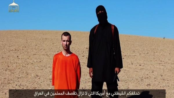 British man David Haines is shown kneeling next to an ISIS militant in newly released video. (Source: ISIS/CNN)
