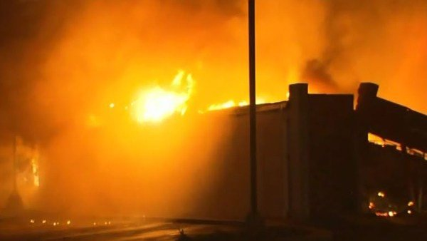Protesters set fire to several buildings in Ferguson, including this auto parts store. (Source: CNN)