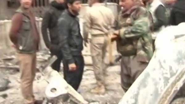 Kurdish and allied forces gather in Kirkuk amid the ruins left by a car bomb. (Source: CNN)