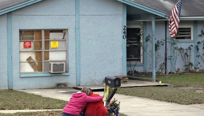 Jeremy Bush, right, is consoled by an unidentified woman Sunday, March 3, 2013, as he sits outside a home where a sinkhole opened up underneath a bedroom, swallowing his brother, Jeffrey Bush, in Seffner, FL. (Source: AP Photo/Chris O'Meara)