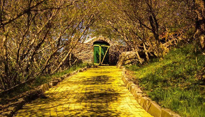 "The yellow brick road leads up to the gates of Oz at the Land of Oz, an abandoned theme park in Beech Mountain, NC. The image is included in the book ""Bizarro,"" which explores amusement parks left behind. (Source: Seph Lawless)"