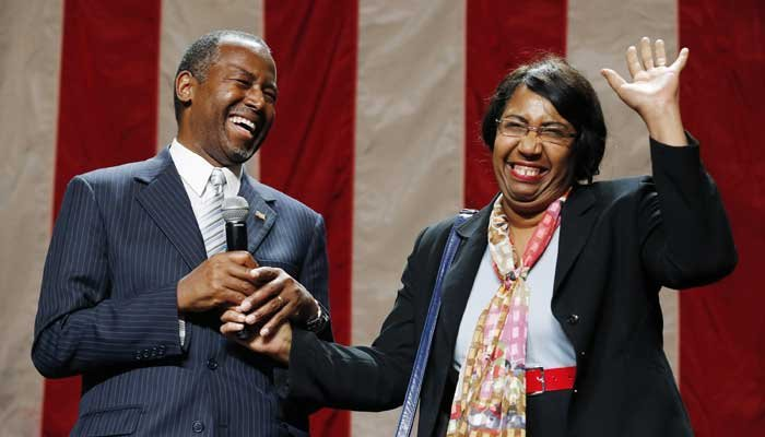 Republican presidential candidate Dr. Ben Carson, left, laughs as his wife, Candy Carson, waves to the crowd after saying a few words to the crowd supporting her husband in front of supporters on Aug. 18, 2015. (Source: AP Photo/Ross D. Franklin)