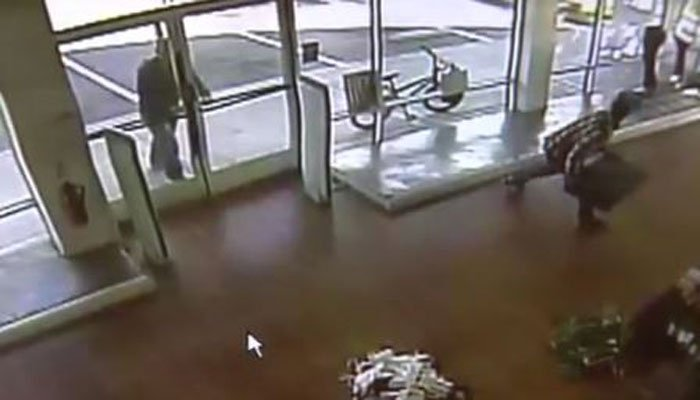 A robbery suspect prepares to throw an object against the glass to try and break out of a store. (Source: KTLA/CNN/Steve Han)