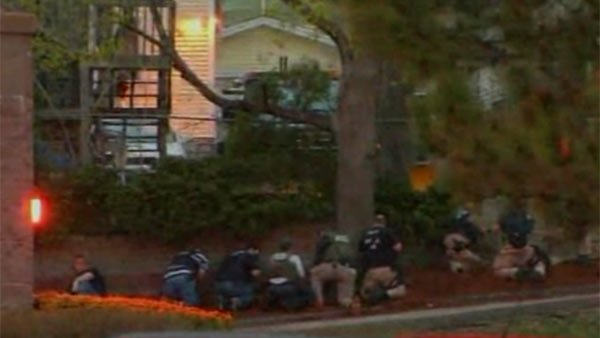 Police gather surround a home in Watertown, MA where the suspect was hiding in the backyard. (Source: CNN)
