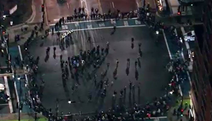 "Protesters in Chicago on Tuesday form a circle in the street and hold up letters spelling ""Laquan,"" the first name of the 17-year-old shot to death by a police officer. (Source: CNN)"