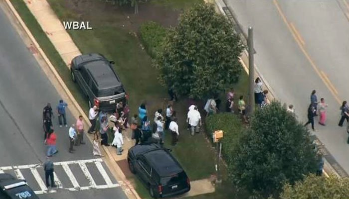 People evacuate from the office where a gunman opened fire at a newspaper in Annapolis. (Source: WBAL/CNN)