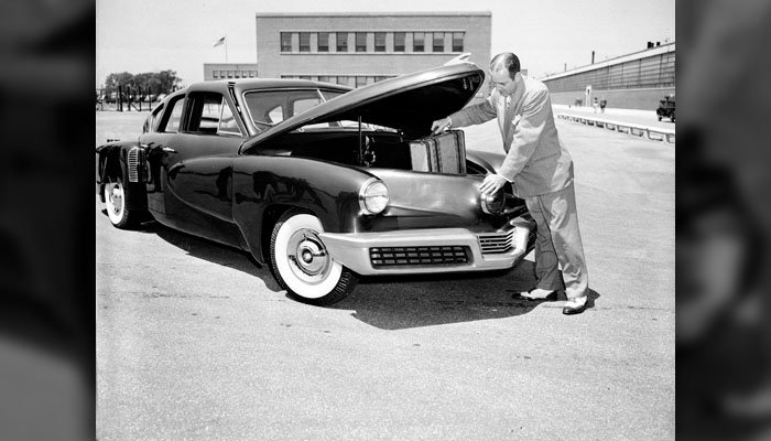Preston Tucker places luggage below the hood as he demonstrates his rear-engine Tucker '48 at the company's southside Chicago plant, on June 20, 1947. (AP Photo/Edward S. Kitch)