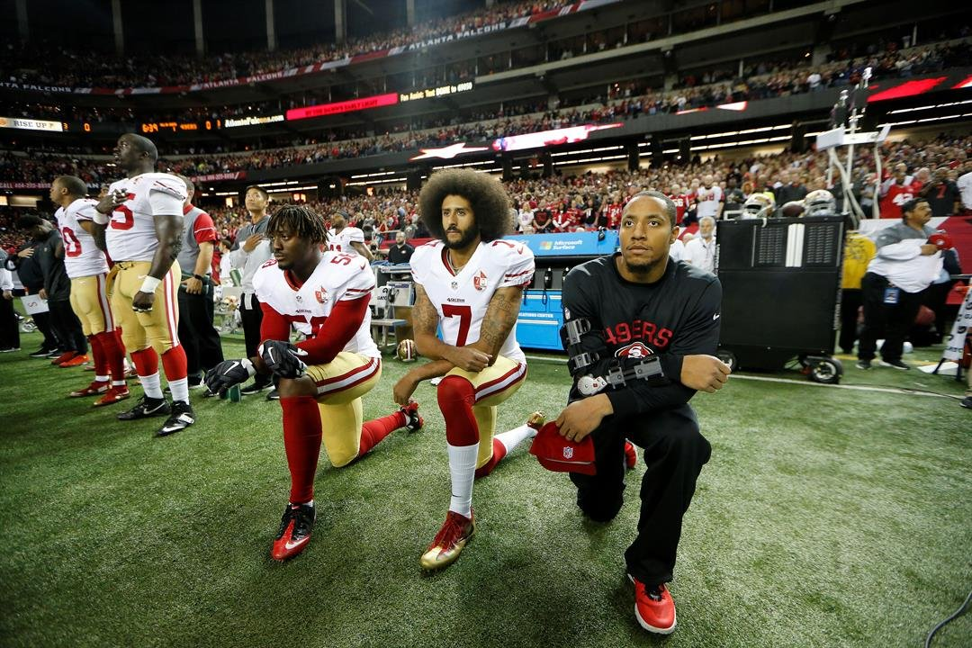 (AP Photo/John Bazemore) San Francisco 49ers quarterback Colin Kaepernick (7) and San Francisco 49ers outside linebacker Eli Harold (58) kneel during the playing of the National anthem before the first half of an NFL football game.