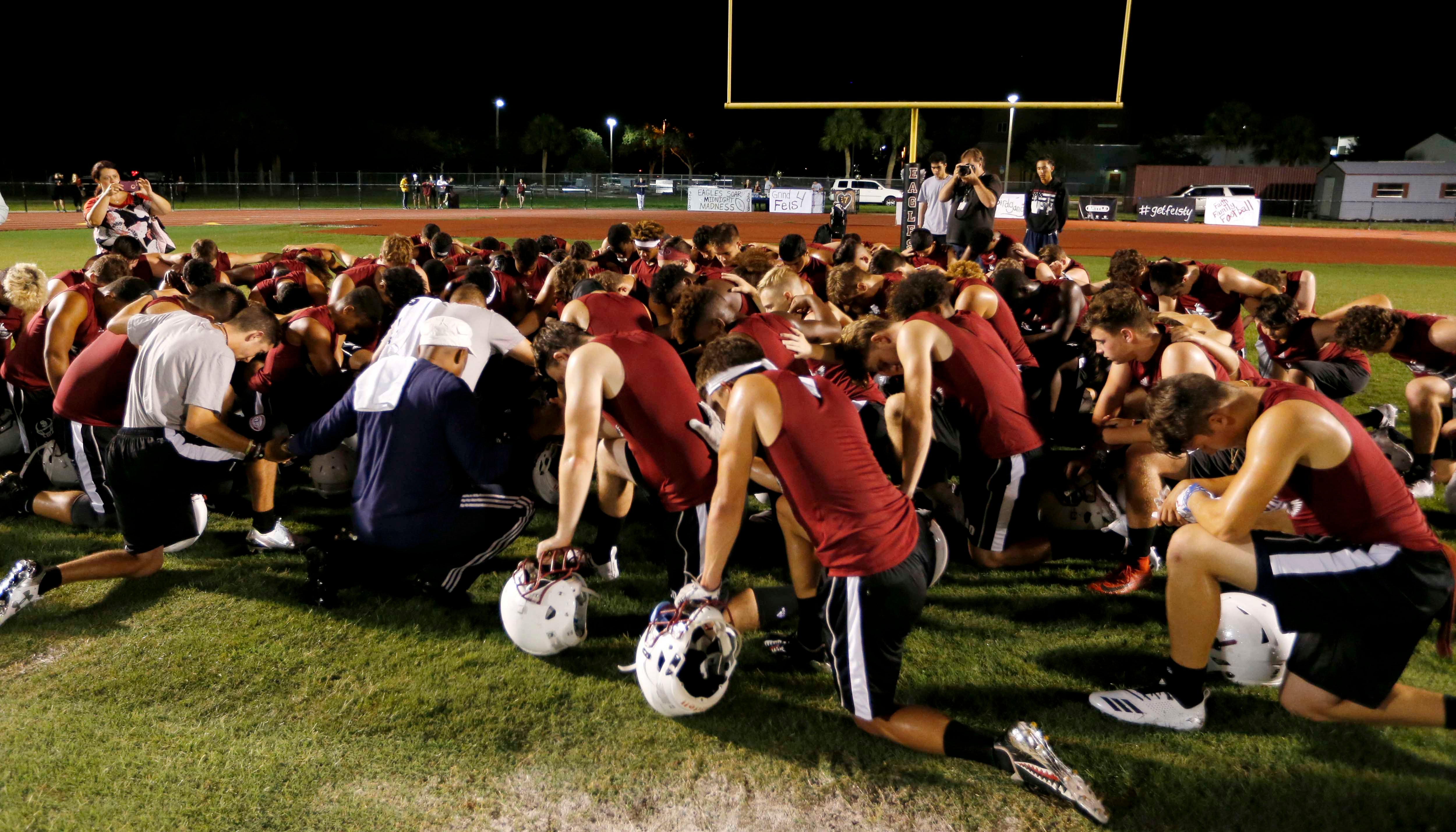 Members of the Marjory Stoneman Douglas High School football team pray together as they began practice for a new season just after midnight on Monday, July 30, 2018, in Parkland, FL. (AP Photo/Joe Skipper)
