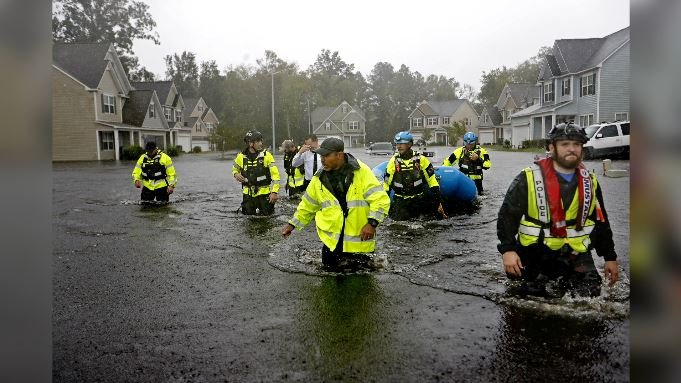Members of the North Carolina Task Force urban search and rescue team wade through a flooded neighborhood looking for residents who stayed behind as Florence continues to dump rain in Fayetteville, N.C., Sunday, Sept. 16, 2018. (AP Photo/David Goldman)